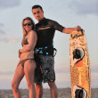 Surf couple posing at beach on sunset - Stock Photo
