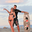 Surf couple posing at beach on sunset - Foto Stock