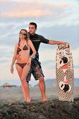 Para surf pozowanie na plaży na zachód słońca — Zdjęcie stockowe