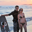 Stock Photo: Surf couple posing at beach on sunset