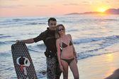 Couple de surf se présentant à la plage sur coucher de soleil — Photo