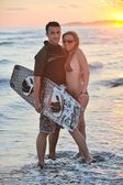 Surf pareja posando en la playa en sunset — Foto de Stock