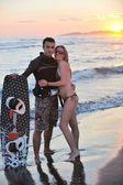 Coppia di surf in posa sulla spiaggia al tramonto — Foto Stock