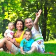 Happy young couple with their children have fun at park — Stock Photo #6726172