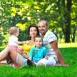 Happy young couple with their children have fun at park — Stock Photo #6728677