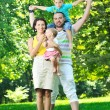 Happy young couple with their children have fun at park — Stock Photo #6728977