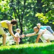 Happy young couple with their children have fun at park — Stock Photo #6729081