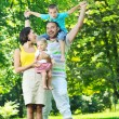 Happy young couple with their children have fun at park — Stock Photo #6729211