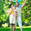 Happy young couple with their children have fun at park — Stock Photo #6729382