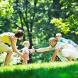 Happy young couple with their children have fun at park — Stock Photo #6729591