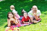 Счастливая молодая пара с их детьми весело провести время в парке — Стоковое фото