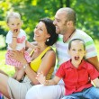Happy young couple with their children have fun at park — Stock Photo #6730438