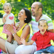 Happy young couple with their children have fun at park — Stock Photo #6730494