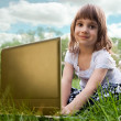 Child with laptop sitting on a meadow — Foto Stock