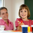 Stock Photo: Elementary school pupil painting under the supervision of a teacher