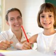 Elementary school pupil working with educator — Stock Photo