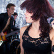 Royalty-Free Stock Photo: Beautiful rock singer with her band in the background