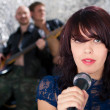 Beautiful rock singer with her band in the background — Stock Photo
