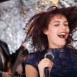 Стоковое фото: Beautiful rock singer with her band in the background