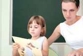 Elementary school pupil working under the supervision of a educator — Stock Photo