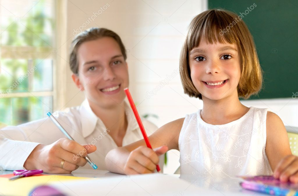 Elementary school pupil working under the supervision of a educator — Stock Photo #6309191