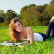 Beautiful уoung woman reading on a green meadow — Stock Photo #6264168