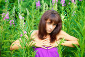 Beautiful young woman posing against a background of green grass — Stock Photo