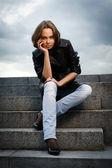 Vacker ung kvinna som sitter på stentrappor — Stockfoto