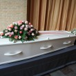 White coffin with pink sympathy flowers — Stock Photo