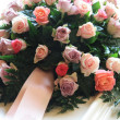 Stock Photo: Pink sympathy flowers on white coffin