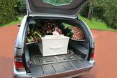 Blanc cercueil dans un corbillard gris — Photo