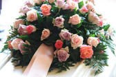 Pink sympathy flowers on a white coffin — Stock Photo