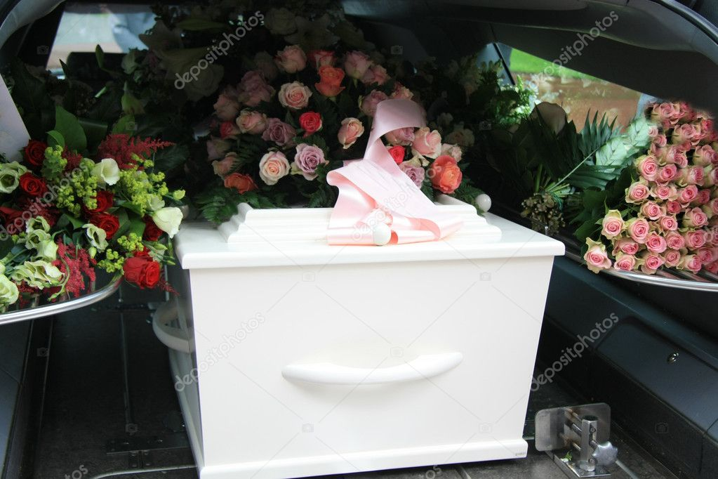 A white coffin, covered with flowers in a grey hearse — Stock Photo #6582397