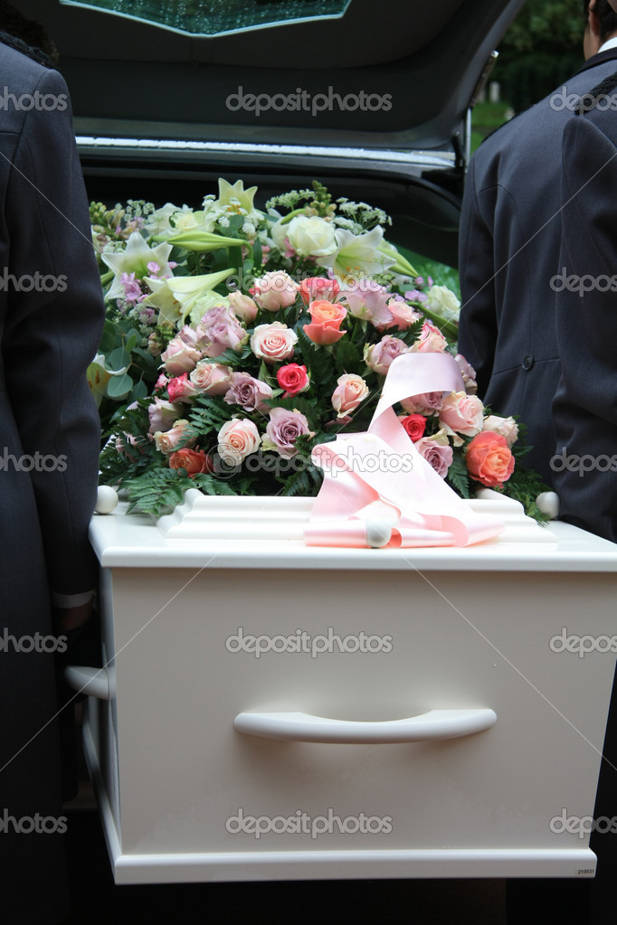 A white coffin, covered with flowers near a hearse, taking out the coffin  Stock Photo #6582417
