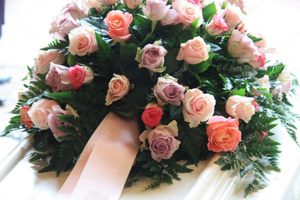 Pink sympathy flowers with a pink ribbon on a white coffin — Stock Photo #6582438