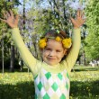Happy child in park with hands up and wreath on head — Stock Photo #5499113