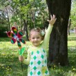 Happy little girl in park with hand up — Stock Photo #5499187