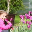 Little girl smell tulip flower — Stock Photo