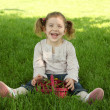Happy young girl sitting on grass in park — Stock Photo