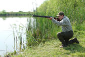 Hunter aiming and ready for shot wild duck hunting — Stock Photo