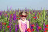 Little girl standing in meadow with colorful flowers — Stock Photo