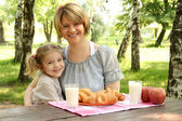 Happy mother and daughter with healthy breakfast — Stock Photo