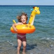 Stock Photo: Happy little girl jumps in the sea