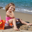 Little girl with toys posing on the beach — Stock Photo