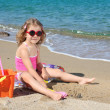 Little girl with sunglasses playing on beach - Stock Photo