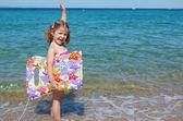 счастливый маленькая девочка, стоя в море с рукой — Стоковое фото