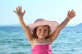 Happy little girl with straw hat and hands up on the beach — Stock Photo