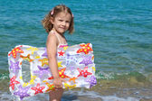 Little girl with airbed standing in the sea — Stock Photo