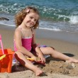 Little girl sitting on beach and playing with toys - Stock Photo