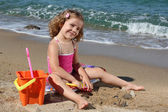 Little girl sitting on beach and playing with toys — Stock Photo